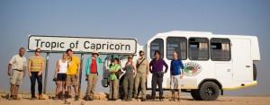 Kleinbus und Reisegruppe am südlichen Wendekreis in Namibia
