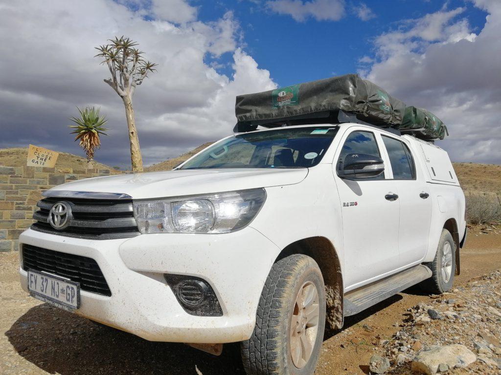Nahansicht vom Toyota Hilux Double Cab mit 2 Dachzelten vor Eingang zum Naukluft-Park in Namibia