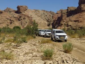 Kolonne von Allradfahrzeugen auf einer steinigen Piste Namibias