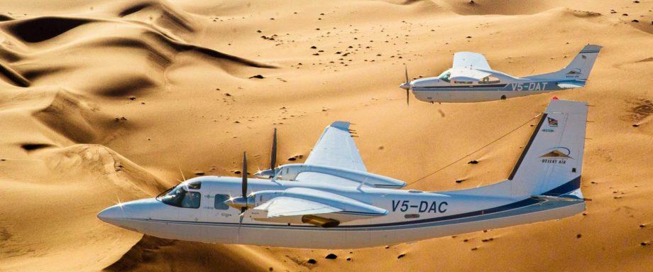 Zwei Flugzeuge - Aero Commander & Cessna 210 gemeinsam vor dem Hintergrund der Dünenlandschaft des Sossusvlei